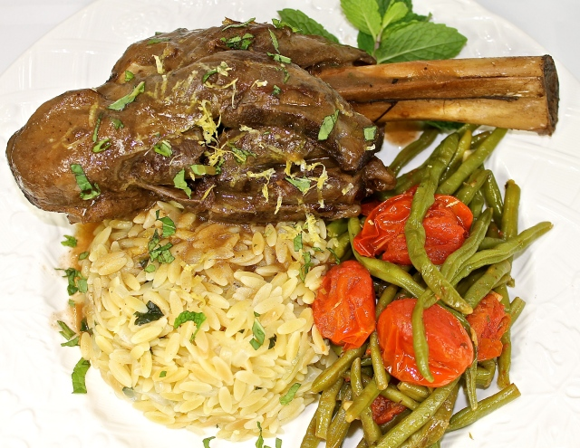 Slow Braised Lamb Shanks Served With Lemon Orzo, Green Beans And Tomatoes