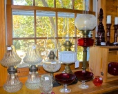Antique Oil Lamps Displayed In A Window To Show Off Their Designs