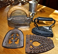 "A Collection Of ""Sad Irons"" And Ironing Trivets"