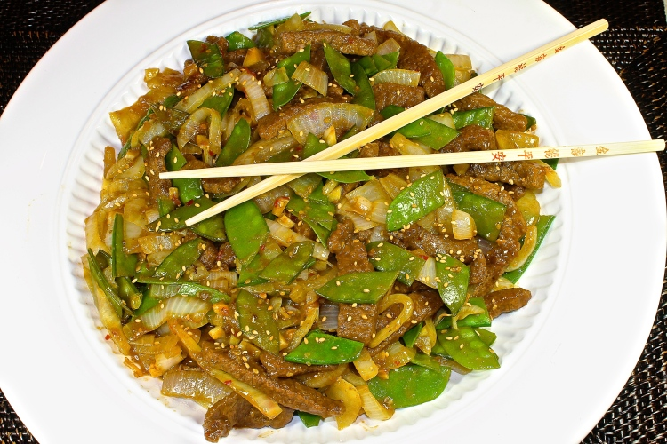A Large Platter Of Sesame Beef With Snow Peas Ready To Serve Dinner Guests